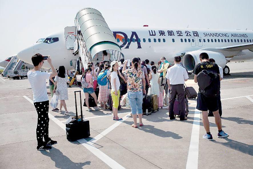 发布时间:2015-07-29 09:28:15   7月27日,在重庆江北机场,重庆到江苏盐城首航乘客在登机。当日,山东航空公司开通重庆-盐城-大连航线,搭建渝苏辽三地方便快捷的空中通道。航线由山东航空公司波音B737-800型飞机执飞,航班号为SC8791/ 2,每日一班,当日往返。新华社发(顾颐 摄)